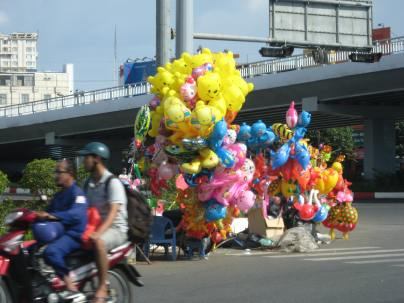 This is a very common sight in Saigon. Selling stuff on the side of the road - balloons here.