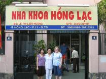 Van (Lam's sister), Lam's Mom and Aunt Karen in front of the clinic and their house.