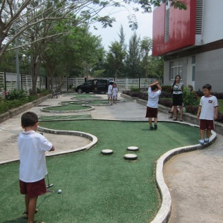 Jacob in the forefront and friends in the background - playing mini golf behind their buidling at school
